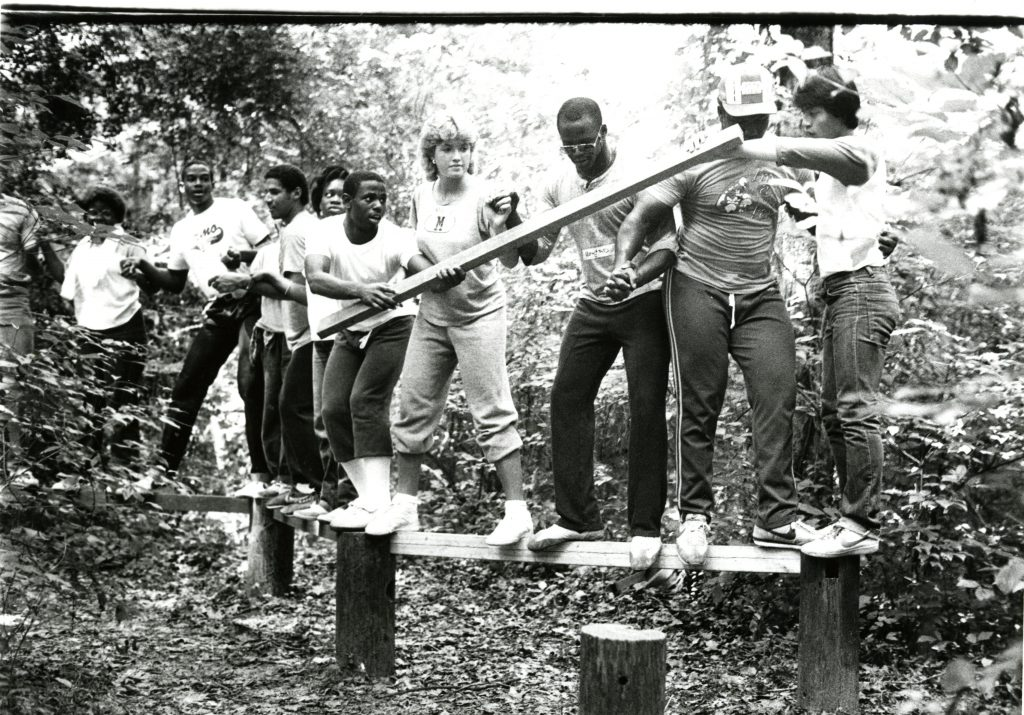A group of about one dozen students balancing on a log as part of the August 1984 FOCUS Davidson College orientation program.